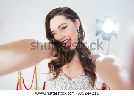 Cheerful woman on red carpet making selfie photo