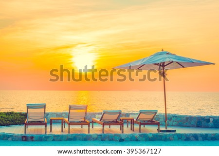 Beautiful luxury hotel swimming pool resort with umbrella and chair - Vintage filter #395367127