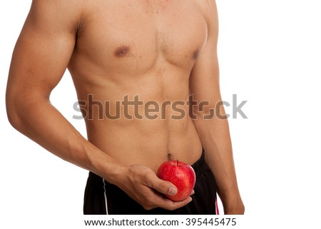 Muscular Asian man show six pack abs with red apple  isolated on white background #395445475