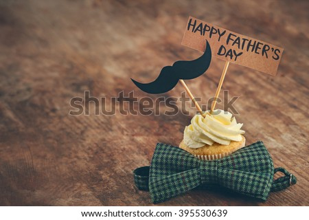 Happy fathers day special cupcake and bow tie on wooden table Royalty-Free Stock Photo #395530639