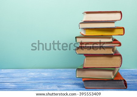 Stack of hardback books on wooden table. Back to school. Copy space for text #395553409
