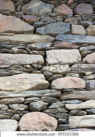 Traditional Georgian wall stacked from mountain rocks. background #395555386