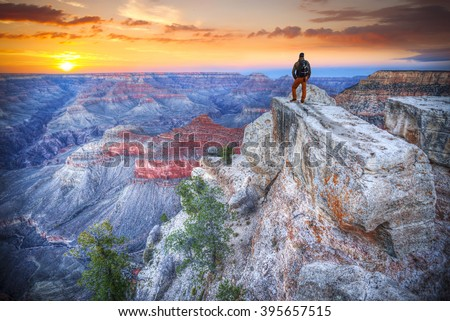 man in the Grand Canyon at sunrise. tourist in America Royalty-Free Stock Photo #395657515