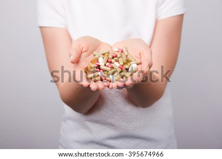 many pills and capsules in women in the hands #395674966
