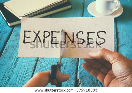 man hand holding card with the word expenses. cutting expenses and costs concept. retro style image Royalty-Free Stock Photo #395918383