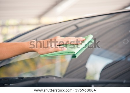 Hand with green microfiber cloth, cleaning glass car.  #395968084