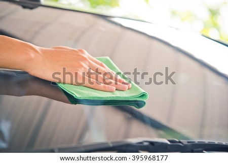 Hand with green microfiber cloth, cleaning glass car.  #395968177