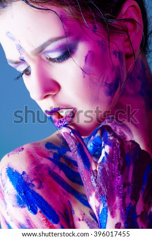 and beautiful young girl with paint on body and hands #396017455