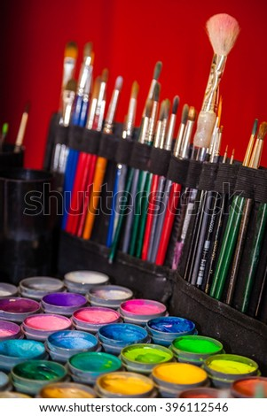 Colorful paint tubes and brushes used for face art painting #396112546