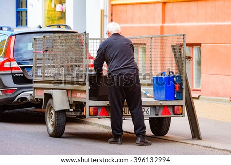 Kristianstad, Sweden - March 20, 2016: One male person is loading a small trailer with stuff. Person seen from behind. Trailer is a rental with netted fence. Real people in everyday life. #396132994