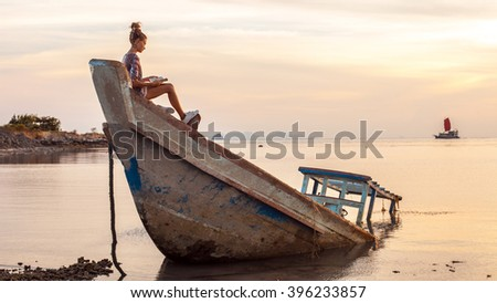 Young woman is sitting on the shipwreck and reading a book. Tropical sunset on the background. #396233857