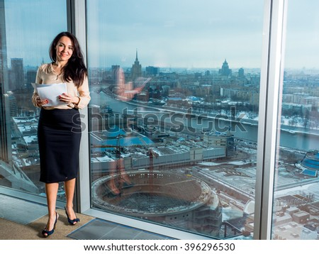 Businessman with papers in the office should have panoramic windows with views of Moscow #396296530