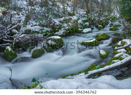snowy river with mossy rocks, Ancares, Galicia #396346762