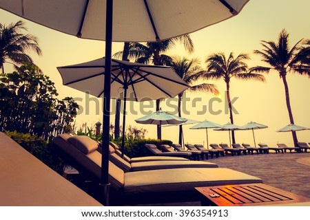 Beautiful Silhouette luxury umbrella and chair around swimming pool in hotel pool resort with coconut palm tree at sunrise times - Vintage Filter and Boost up color Processing #396354913