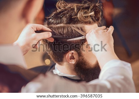 Professional barber styling hair of his client Royalty-Free Stock Photo #396587035