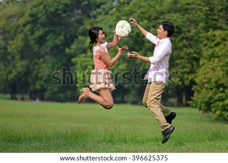 Couple man and woman jump on meadow field at park  #396625375