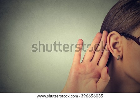 Woman holds her hand near ear and listens carefully isolated on gray wall background  Royalty-Free Stock Photo #396656035