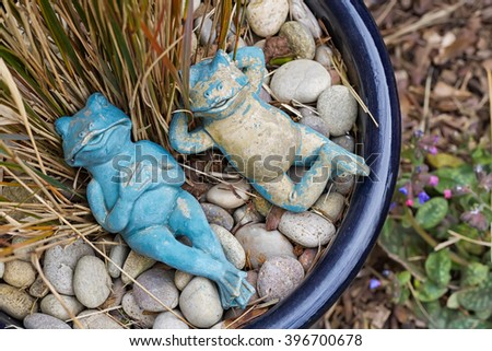 Two relaxing blue and beige garden frogs figures lying in a plant pot as a garden decoration, artificial toy