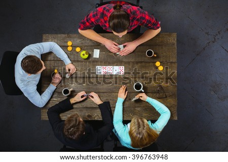 Top view creative photo of friends sitting at dark wooden vintage table. Friends having fun while playing cards #396763948