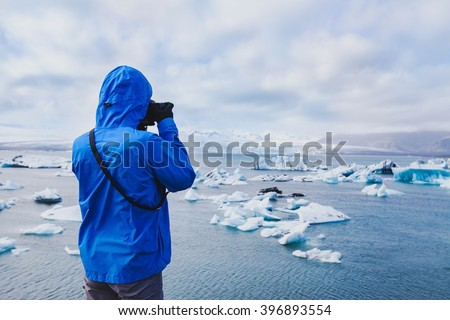 nature travel photographer, person taking photo of arctic icebergs in Iceland