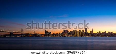 San Francisco skyline at dusk with city lights and the Bay Bridge