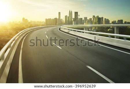 Highway overpass motion blur with city background . #396952639