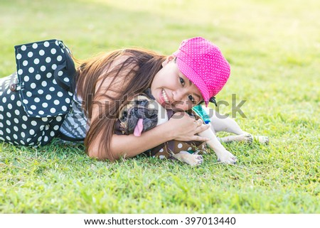 Portrait of a asian teenage woman girl hug with her cute dog puppy pug outdoors on fields #397013440