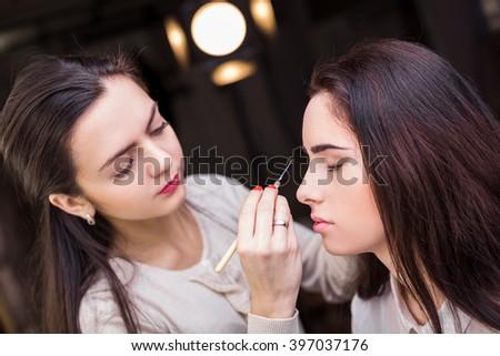 Makeup artist apply makeup to a model.  #397037176