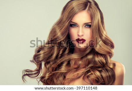 Beautiful girl with long wavy hair .  fair-haired  model  with curly hairstyle   and fashionable makeup . Bright purple lips #397110148