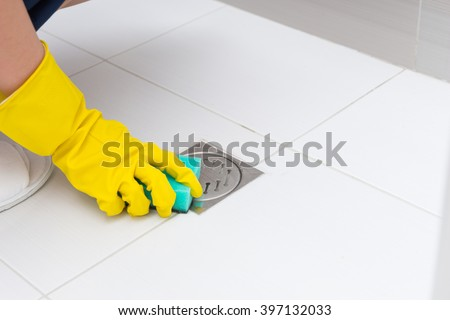 Close up detail view on unidentifiable rubber gloved hand cleaning shower stall floor drain with green sponge #397132033