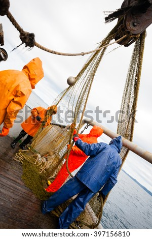 Fishermen in waterproof suits on the deck of the fishing vessel. Morning time. #397156810