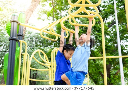 Young asian boy hang the yellow bar by his hand to exercise at out door playground under the big tree. #397177645