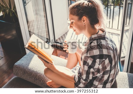 Young pretty woman  sitting at opened window drinking coffee and reading a book enjoys of rest #397255312