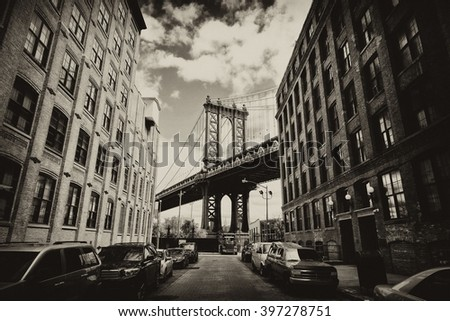 Manhattan bridge seen from a brick buildings in Brooklyn street in perspective, New York, USA. Business and travel background. Vintage, retro postcard with sepia filter. #397278751