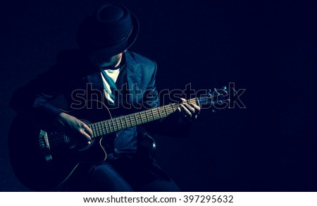 Musician playing the guitar on black background,music concept Royalty-Free Stock Photo #397295632