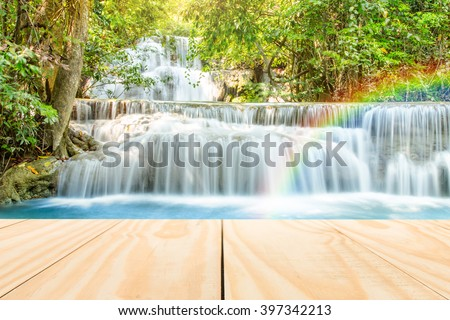 images Wood table top on blur natural waterfall background - can used for display or montage your products