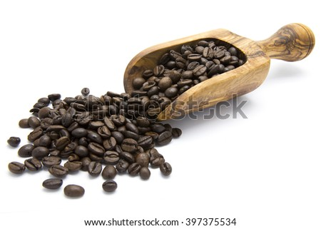 Roasted coffee beans in wooden scoop on white isolated background #397375534