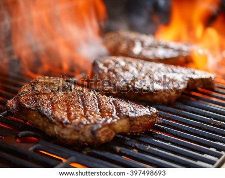 grilling steaks on flaming grill and shot with selective focus #397498693