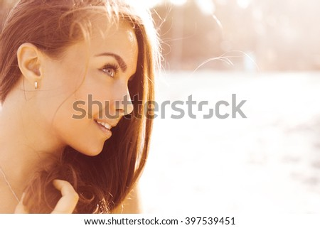 close-up portrait of a beautiful young brunette  Tanned girl on a sunny day in the summer on the beach by the sea smiling at sunset i lifestyle  #397539451