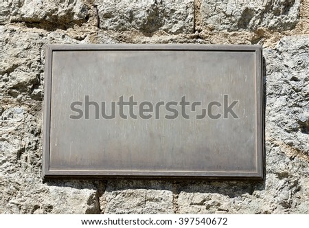 Metal plaque mounted on an old stone wall. #397540672