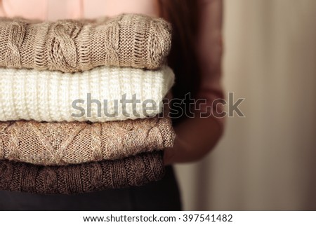 Stack of knitted clothes in female hands closeup #397541482