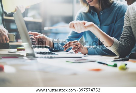 Team brainstorming process. Photo young creative managers crew working with new startup project in modern office. Contemporary notebook on wood table. Horizontal, film effect Royalty-Free Stock Photo #397574752