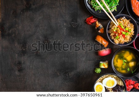 Sushi and japanese food on dark background. Sushi rolls, hiyashi wakame, miso soup, ramen, fried rice with vegetables, nigiri, soy sauce, chopsticks. Asian/Japanese food frame. Overhead     #397650961