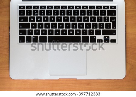 A keyboard of a laptop computer on a wooden table #397712383