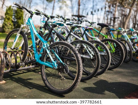 Various bicycles on a rack, available for rent Royalty-Free Stock Photo #397782661