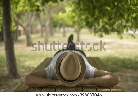 Restful young man wearing a straw hat laying down on a wooden table in the middle of the forest at a park Royalty-Free Stock Photo #398037046