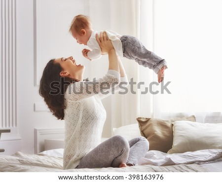 happy loving family. mother playing with her baby in the bedroom. Royalty-Free Stock Photo #398163976
