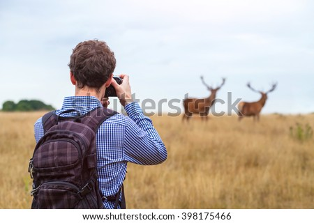 photographer taking photo of wildlife, man with camera and two deers in the nature