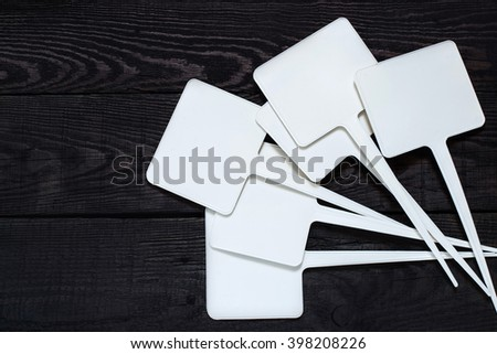 Small plastic pointers for gardeners on a dark wooden table