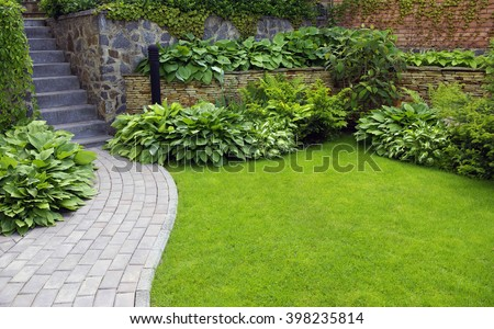 Garden stone path with grass growing up between the stones  #398235814